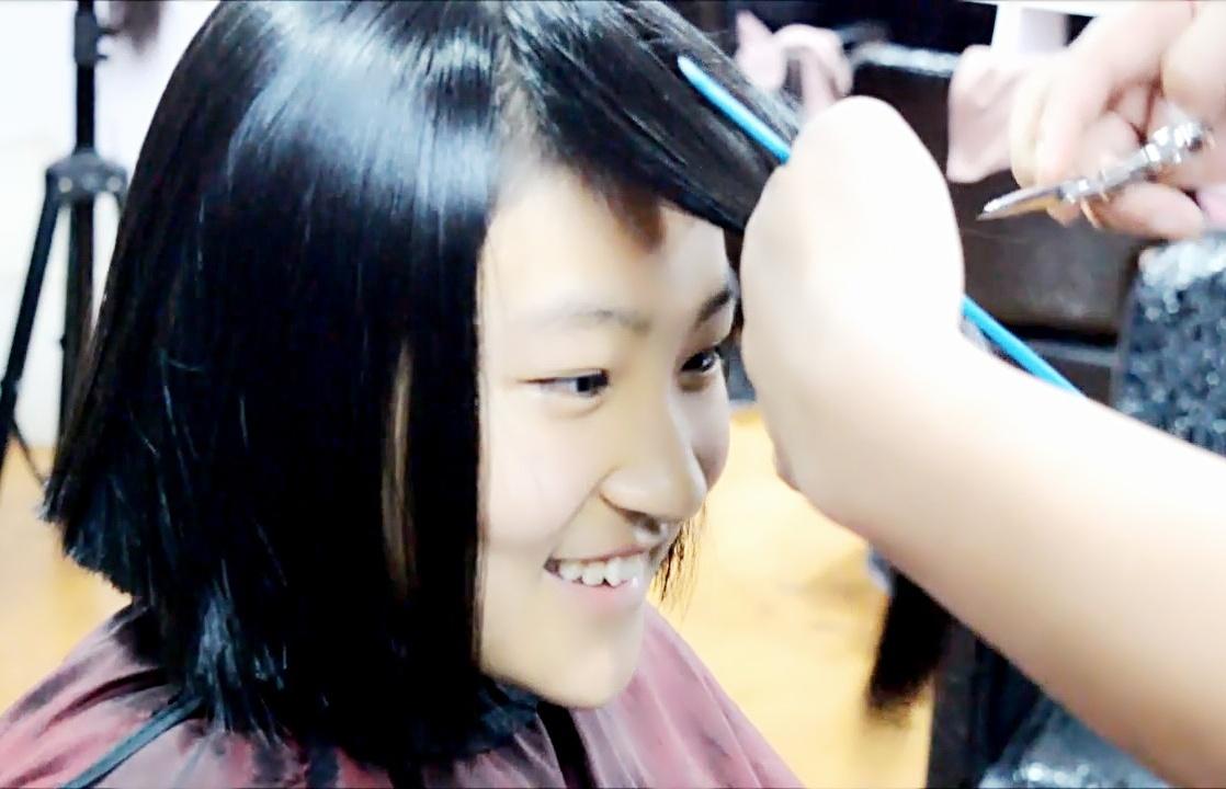 Young girl's longhair cut in barbershop