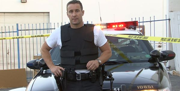 Police man models Bullet Proof vest with Cop car in background